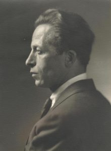 Black and white archival photo showing Albert Gilles in profile, dressed in a suit and tie, looking to the left
