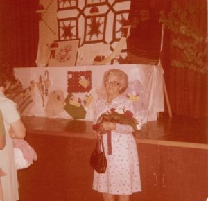 Colour photo of Amanda Gagnon Jalbert holding a bouquet of flowers. She is wearing a white print dress and holding a handbag. On the stage behind her, textile handicrafts are displayed on a table.