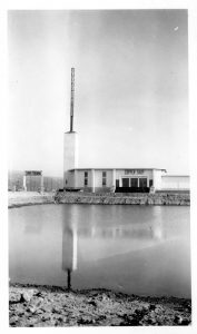 "Black and white archival photo showing a modern, two-storey building beside a road, with a chimney at the far left. In front, the building can be seen reflected in a body of water. On the left, a large sign reads ""Christorama."" It also says ""Copper Shop"" and ""atelier de cuivre"" on the building."