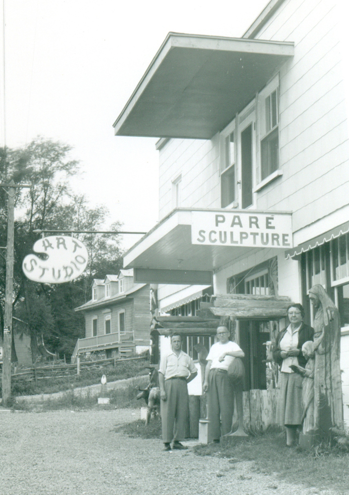 "Black and white archival photo. Louis-Philippe Paré, Alphonse Paré, and an unidentified woman are standing facing the camera by the side of the road in front of a two-storey building. Two signs on the façade of the building read ""Paré Sculpture"" and ""Art Studio."" A house can be seen in the background. Several wooden sculptures stand in front of the building, on either side of the front entrance."