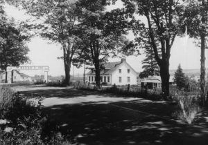 "Black and white archival photo showing a signpost arch over the lane leading to a white inn that can be sign from a side angle on the right. It reads ""The Baker's Inn."" The inn has a gabled roof with three dormers in front and a chimney at either end. There are six windows on the front of the building. Mature trees line the lane leading to the inn."