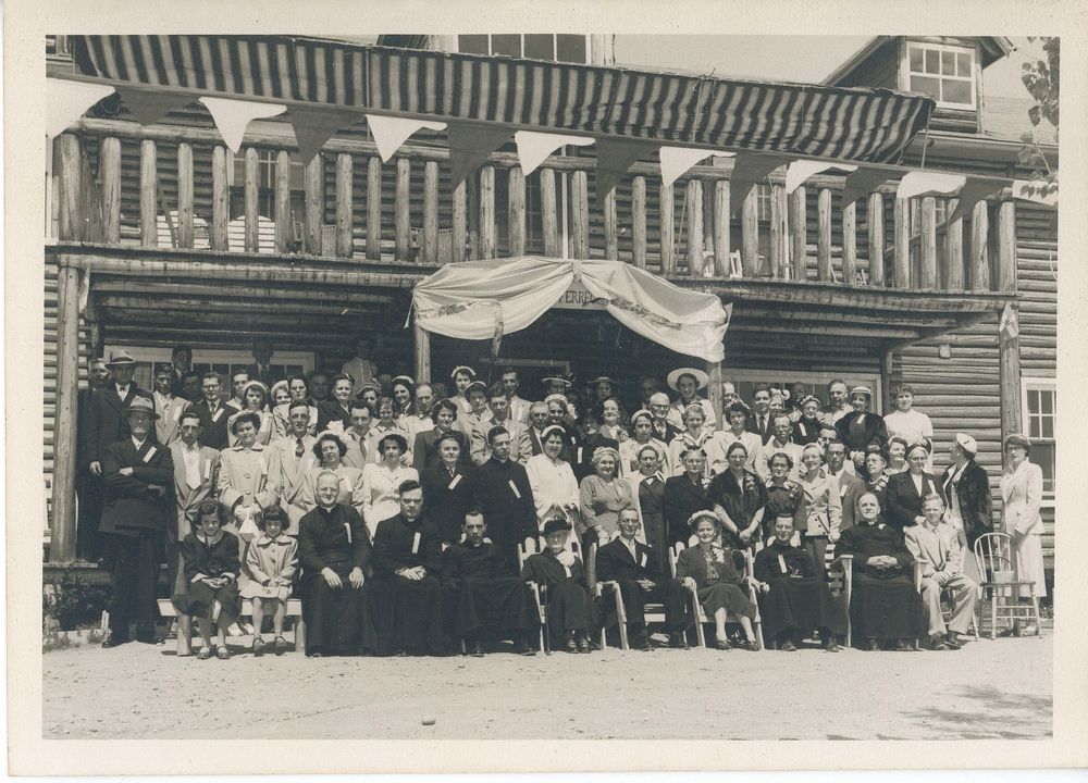 Black and white archival photo of a large group gathered in front of Auberge du Lac. The guests are seated or standing in five lines, and they include members of the clergy, young children, women, and men. The log building behind them stands two storeys tall. The upper floor has a wooden balcony from which a decorative banner hangs.