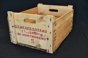 "Colour photo of a wooden crate with the name ""Ferme des coteaux St-Joachim Co. Montmorency S"" stamped on the end facing the camera."