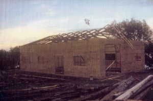Colour archival photo of a building under construction. We can see the wooden walls as well as the roof trusses, also in wood. In the foreground and alongside the building are piles of lumber and logs.
