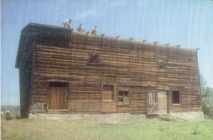 Colour archival photo of a wooden barn with stone foundations. We can see two windows on the upper floor and two doors and three windows on the lower floor. Three men are at work taking the roof apart.