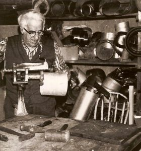 Black and white archival photo depicting Joseph Drouin at work in his workshop. He is operating a machine with his right hand while holding the object he is making in his left. On the table in front of him are a number of tools such as hammers and a mallet. The shelves in the background are piled high with various metal objects.
