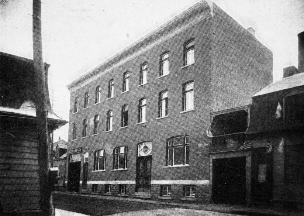 "Black and white archival photo depicting a three-storey building (plus basement). The two upper floors each have eight windows. The ground-floor façade features three windows and three doors, including a larger one on the left. Above this door is a sign marked ""Richard & Cie."" The building shares party walls with the adjacent structures."