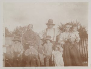 Black and white archival photo of a family standing outside, with a fence and some trees in the background. Hugh Brown is in the centre of the photo wearing a hat. A woman stands on either side of him. The one on the right is holding an infant in her arms. Four young children are standing in front of the adults.