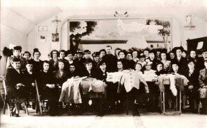 Photographie d'archives en noir et blanc où un groupe de femmes alignées sur deux rangs posent pour la caméra dans une grande salle. Le premier rang est composé de femmes assises, tandis que celles du deuxième rang sont debout. Un seul homme, un abbé, se trouve au centre. Des tables placées à l'avant du groupe montrent des pièces d'artisanat textile.