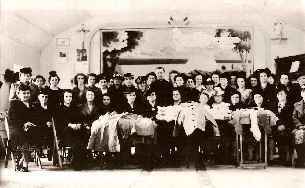 Black and white archival photo showing a group of two rows of women posing for the camera in a large room. Those in the front row are seated, with the others standing behind. The only man in the photo, a priest, stands in the centre. Various textile handicrafts are displayed on tables in front of the group.