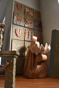 Photographie couleur de l'intérieur d'une église. Les fonts baptismaux, au centre, sont composés d'un immense coquillage et leur base présente des motifs de vagues. Sur le mur à l'arrière, les tableaux sculptés dans le bois et peints illustrent des scènes bibliques où l'eau et les vagues constituent un motif central.
