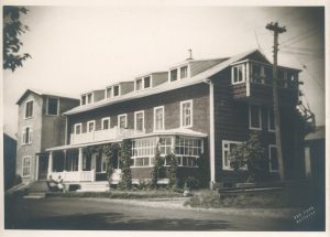 Black and white archival photo showing a three-storey, gable-roofed hotel. The main façade boasts a balcony and a veranda, and there is a solarium on the ground floor.