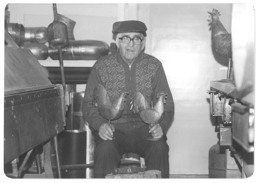 Black and white archival photo of Joseph Drouin in his later years, seated in his workshop and holding two cooper roosters on his lap. On a shelf behind him on the left, we can see pieces of metal pipe. On the right, a larger copper rooster perches on his workbench.