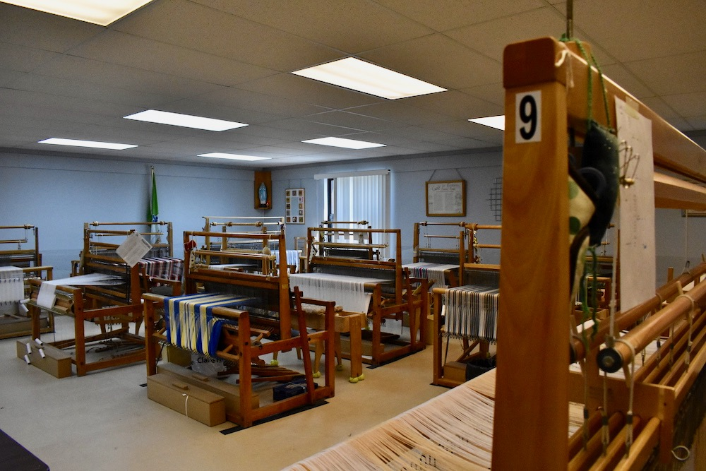 Colour photo of a room with more than ten large looms.