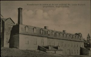 Black and white archival photo showing a three-quarter view of an industrial, three-floor building with multiple windows and a mansard roof. A tall chimney stands behind the building to the left. Two lower chimneys emerge from the centre of the factory.