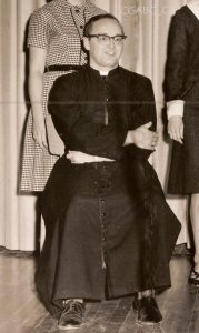 Black and white archival photo showing vicar Jean Moisan sitting with his arms crossed. He is wearing glasses, a cassock, and dark-colour shoes. Two women, their faces partially hidden, are standing behind him.