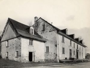 Black and white archival photo showing a distant view of the façade and left profile of a three-storey gabled building made of stone partially covered with lime mortar. A smaller annex can be seen on the left.