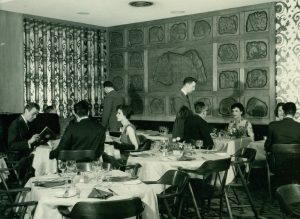 Photographie d'archives en noir et blanc montrant une salle à manger occupée par des serveurs et des clients attablés. Au fond de la salle, on aperçoit une murale en bois sculptée où un motif central est entouré de vingt-deux panneaux plus petits.