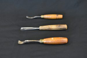 Colour photo showing three wood-handled gouges with different shaped blades against a black background.