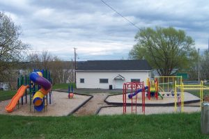 Photo of a park showing a small white building with a door and three windows on the façade looking over a series of playground modules. On the left is a spiral slide and a straight slide, as well as climbing modules, while on the right we can see swings and a smaller slide. The park is surrounded by grass.
