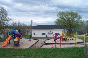 Photographie d'un parc où se trouvent un petit bâtiment blanc muni d'une porte et de trois fenêtres et, devant celui-ci, des modules de jeu pour les enfants. À gauche, on aperçoit un toboggan en colimaçon, une glissade et des jeux pour grimper et, à droite, des balançoires ainsi qu'une plus petite glissade. Le parc est entouré de gazon.