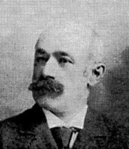Black and white, three-quarter-view, archival portrait photo of a moustachioed Arthur Toussaint wearing a suit and tie.