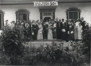 "Black and white archival photo showing a bride and groom surrounded by their elegantly dressed guests in front of Auberge Baker. Everyone is looking at the camera. Behind the group, above the door, hangs a sign reading ""ALL YOU CAN EAT 50₵."" In the foreground are plants and bushes."