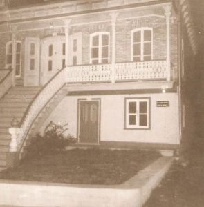 Black and white archival photo of a brick, two-storey home. The ground floor of the house, clad in white stucco, is lower than the upper storey. A staircase leads up to the veranda and to the main entrance on the upper floor. Narrow pillars support the veranda roof. A smaller door next to a window provides access to the ground floor.