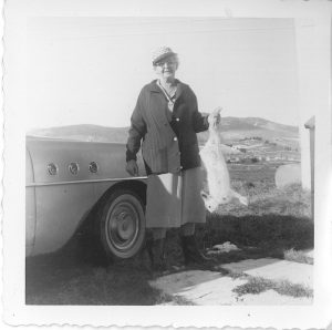 Black and white archival photo depicting an elderly Rose Lachance wearing a cap, a knit cardigan, a skirt, and rubber boots. She is holding up a dead hare in her left hand. She is standing next to a vehicle, and in the background we can see fields and hills.