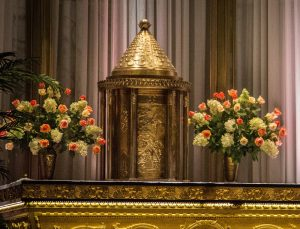 Colour photo of an ornate, embossed metal, cylindrical tabernacle set on an altar between two large vases of pink and white flowers. The top of the tabernacle is a conical shape.