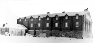 Black and white archival photo showing the A. Toussaint & Cie winery, a large, two-storey brick building. The façade features two rows of eight windows.