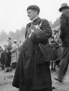 Albert Tessier se tient, caméra à la main, sur une plage au milieu d'autres spectateurs de la course de canots.