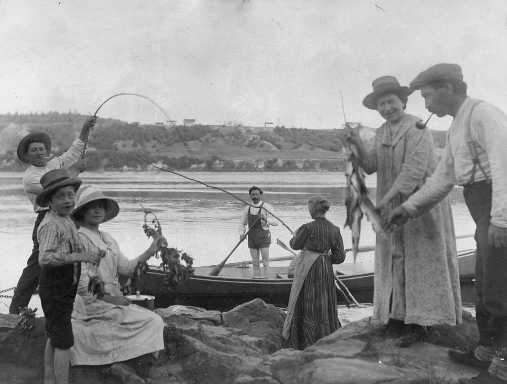 A family is fishing on the banks of the Saint-Maurice. A young boy is holding a fishing rod and a woman is holding up several fish.