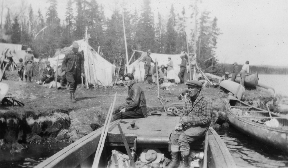 Several men, women and children are busy in a rudimentary camp set up on the banks of a river.