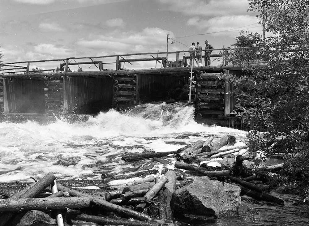 Three men are standing on a dam made of logs. A gate in the dam is open, allowing a torrent of water and logs to pass through.