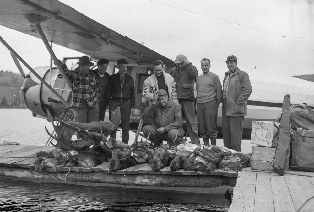 Eight men pose on a dock in front of a seaplane with four moose carcasses.