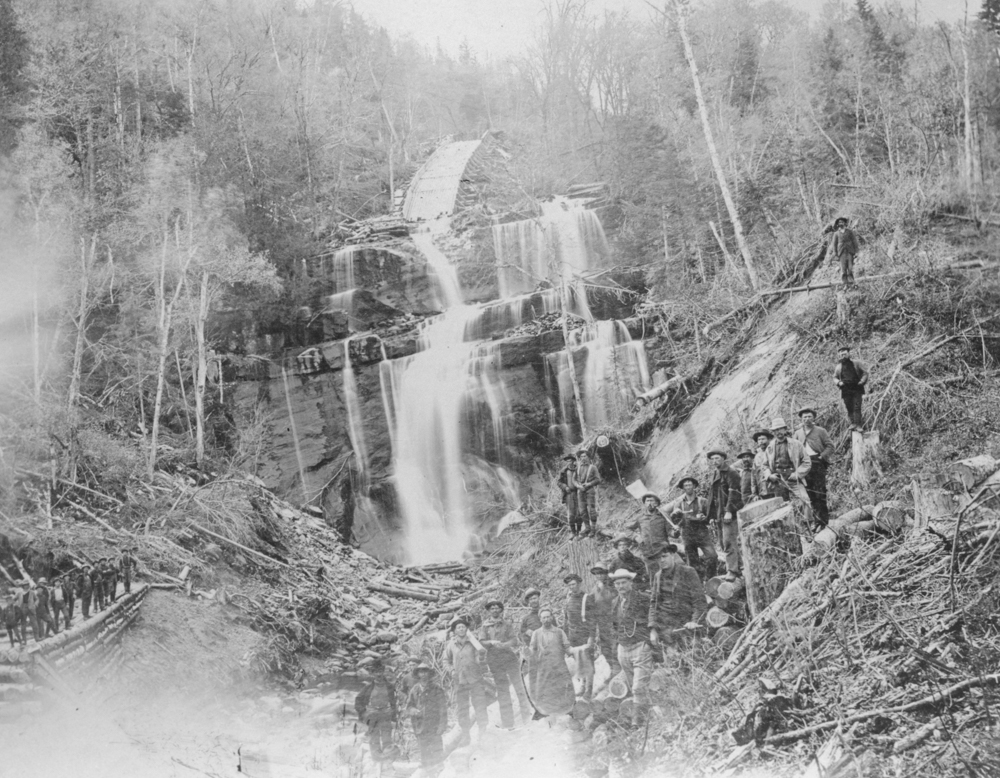 Several workers pose at the bottom of a waterfall where they built a ramp for logs.