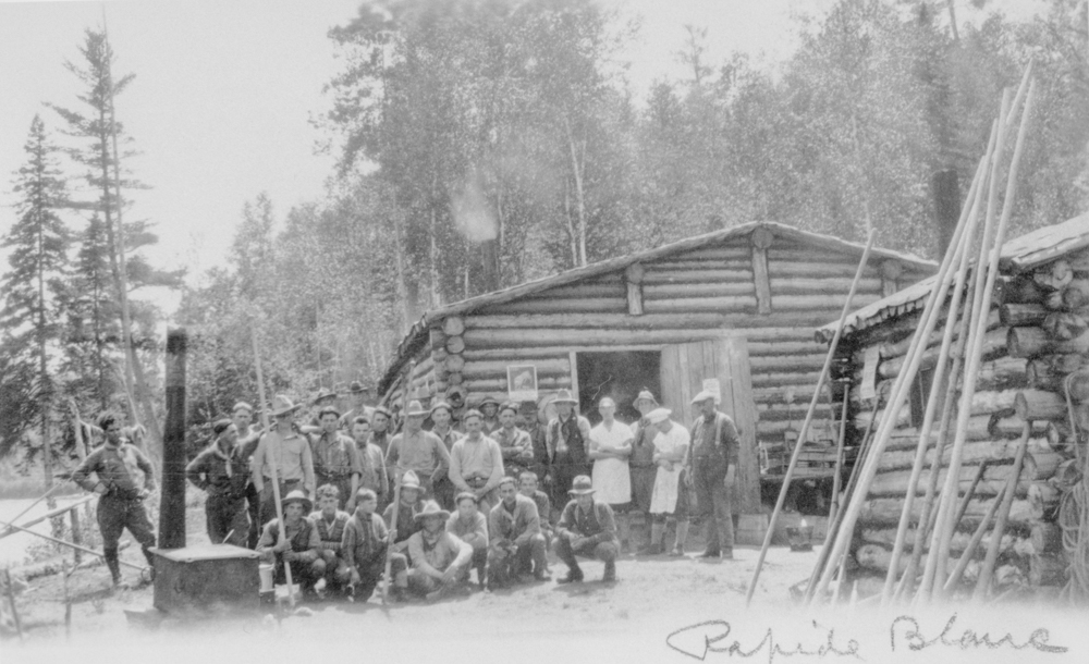 A group of workers pose in front of small log cabins in the middle of the forest.