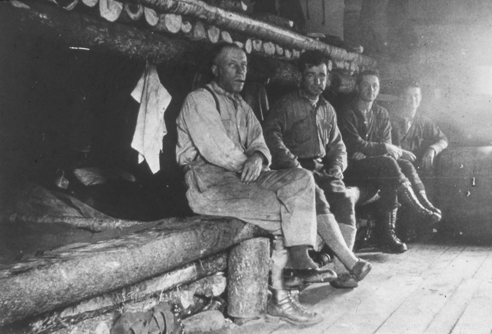 Des hommes sont assis sur des lits faits de sapinage et de rondins grossièrement taillés.
