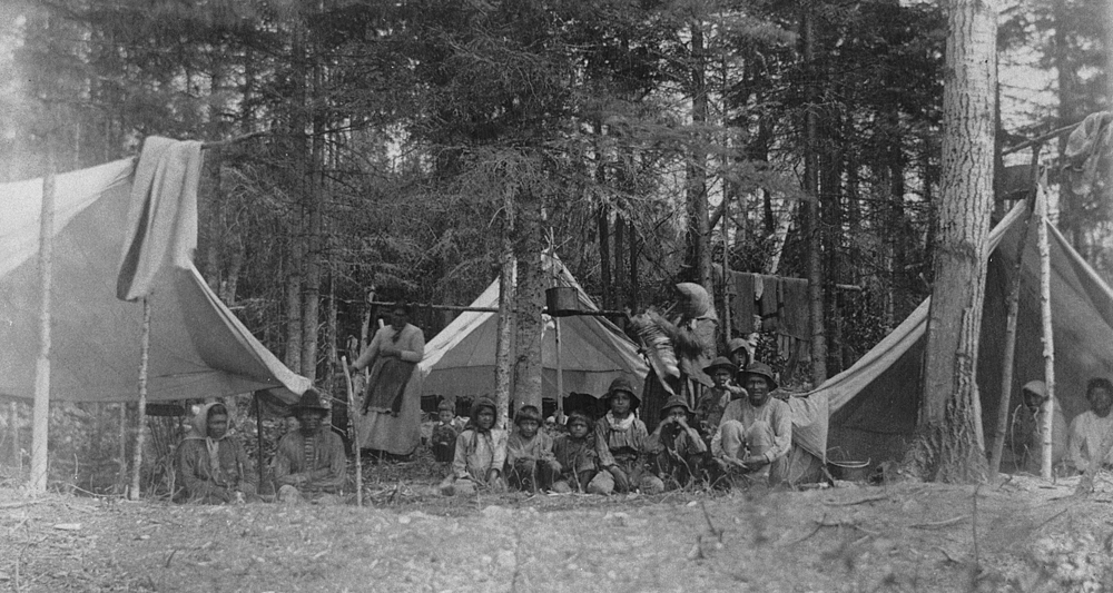 Indigenous people of all ages pose in the midst of rudimentary tents surrounded by tall coniferous trees.