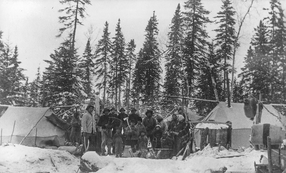 Indigenous people of all ages pose in the snow amidst rudimentary tents in the forest