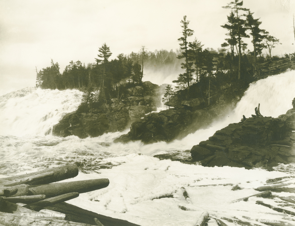 The water falls violently down the Shawinigan Falls, divided into three sections, through rocks and piles of logs.