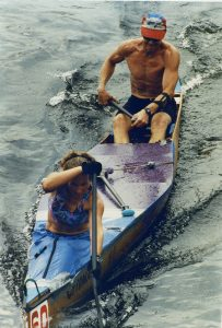 A man and a woman sit in a canoe, both rowing hard.