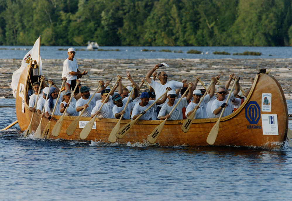 20 men and women are rowing to move a large rabaska forward.