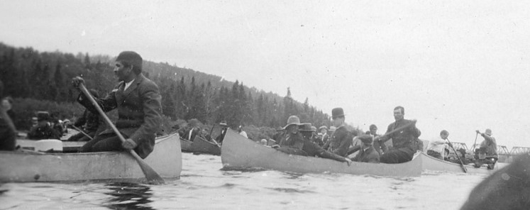 Indigenous people are sitting in canoes filled with belongings on the river.