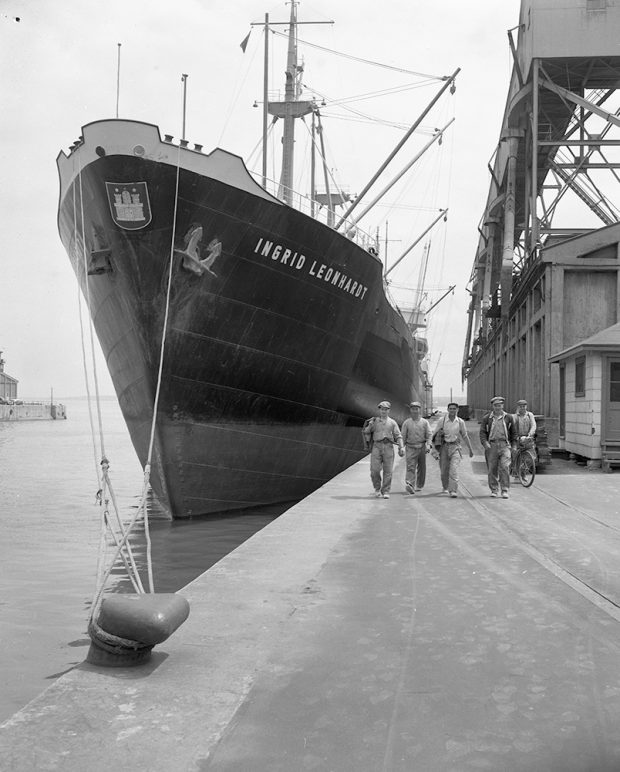 Men walking on a quay in front of the huge bow of a docked ship.