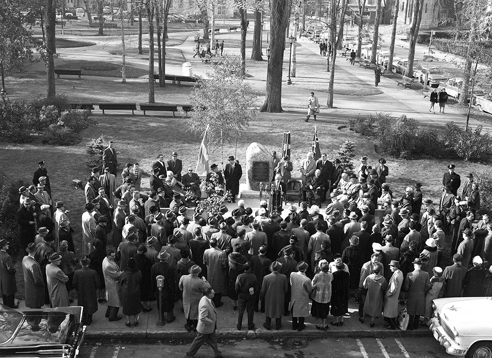 A crowd is gathered near a park. People are gathered in front of a large rock on which a bronze plaque is placed. A man addresses the crowd in front of microphones.
