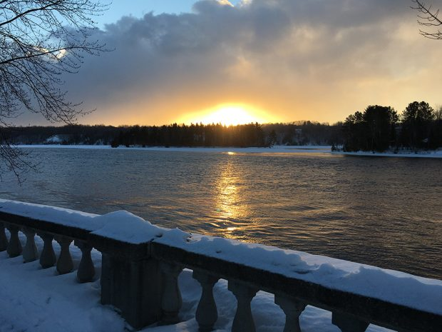 The sunset is reflected on the river water. A snow-covered railing is in the foreground.