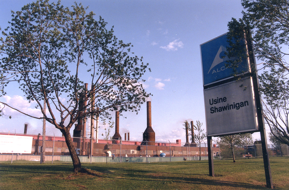 The foreground is occupied by a sign that says: Alan, Usine Shawinigan (Alan, Shawinigan Plant). In the background, behind a fence, the factory and its chimneys dominate the landscape.