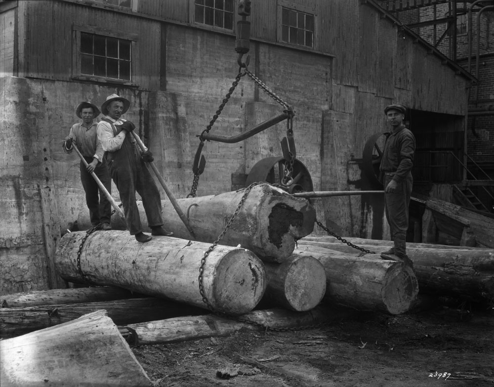 In front of the factory, three men are standing on large trunks that are tied together with chains.
